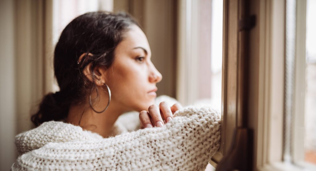 Worried woman looking out window