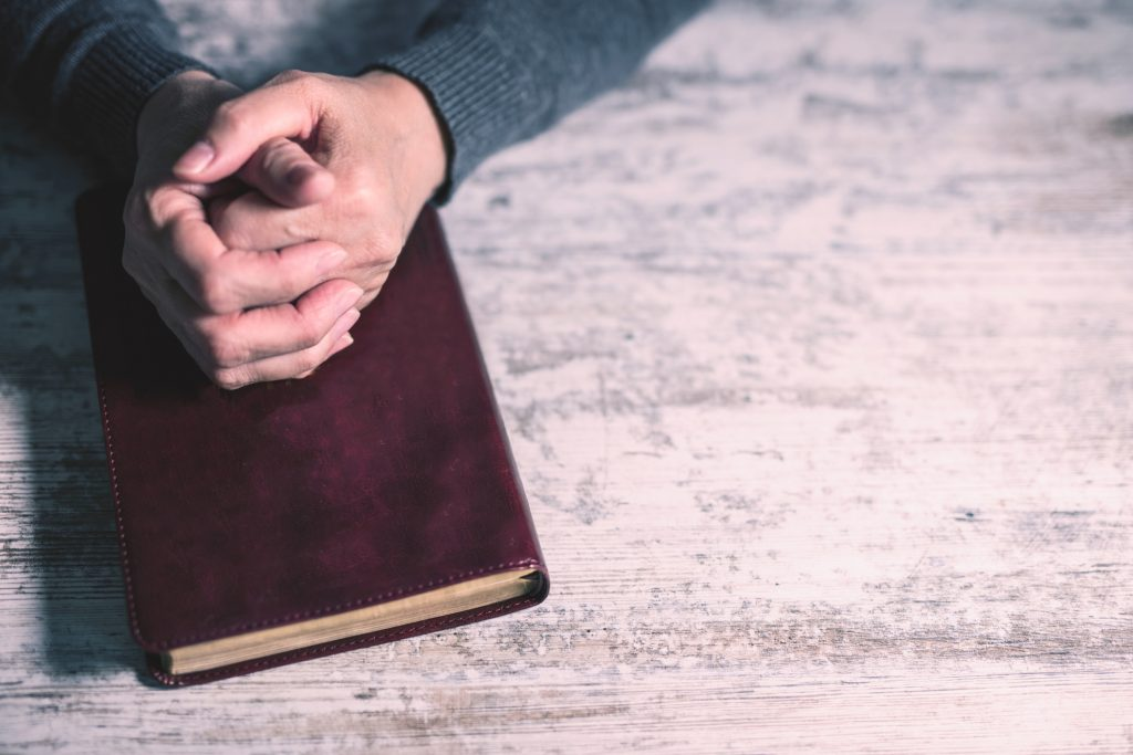 Folded hands on Bible