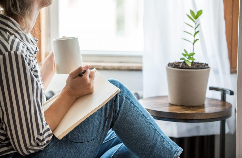 Woman relaxing writing in journal