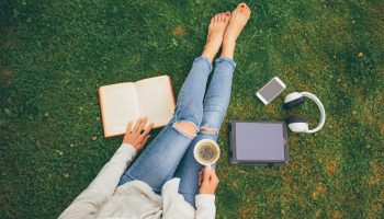 Top view of woman reading in grass