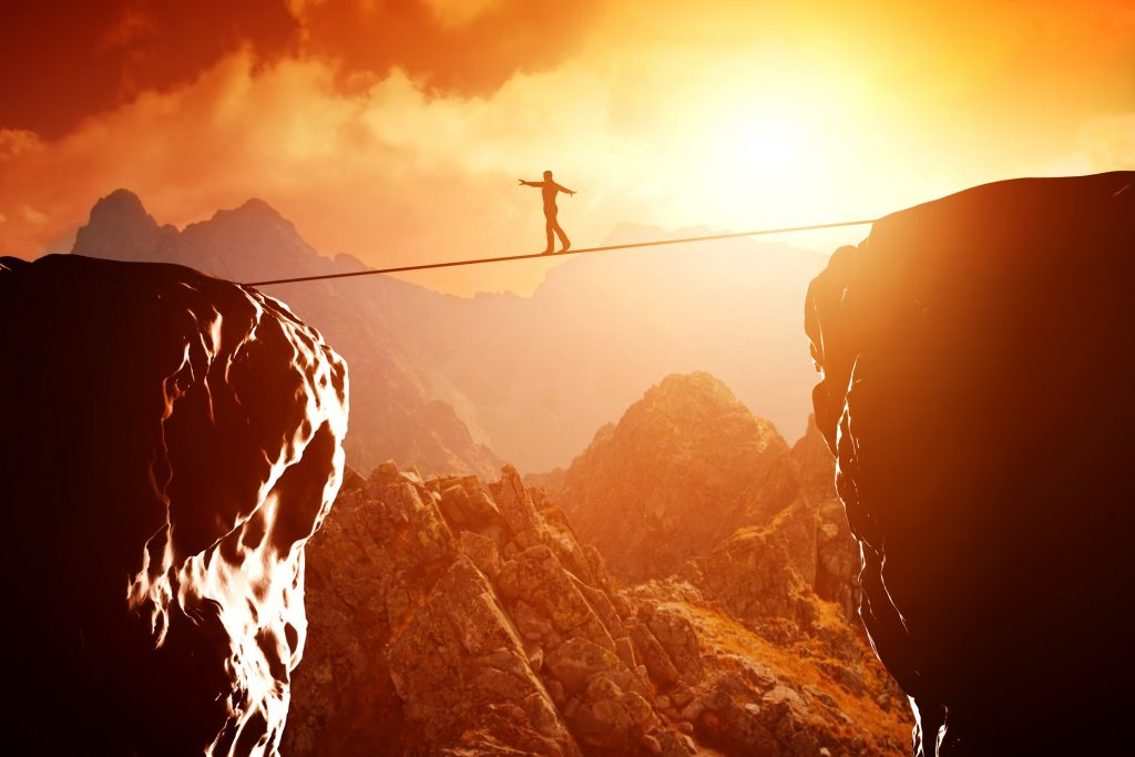 man walking on tension rope over canyon