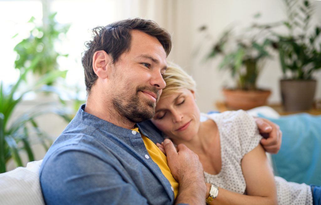 Front view of happy couple in love sitting indoors at home, hugging.