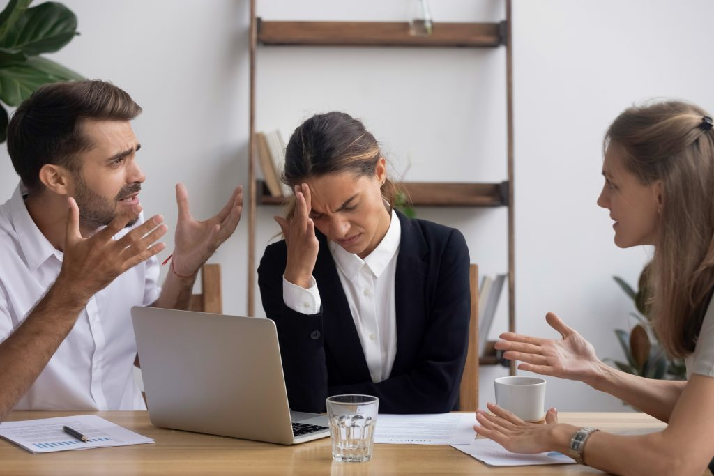 stressed employee dealing with toxic co-worker in office meeting
