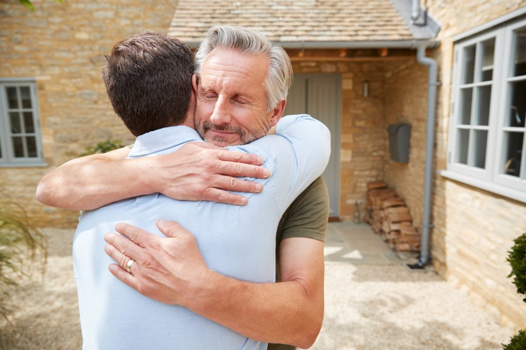 Senior Father Greets And Hugs Adult Son Outside Front Door Of House As He Visits