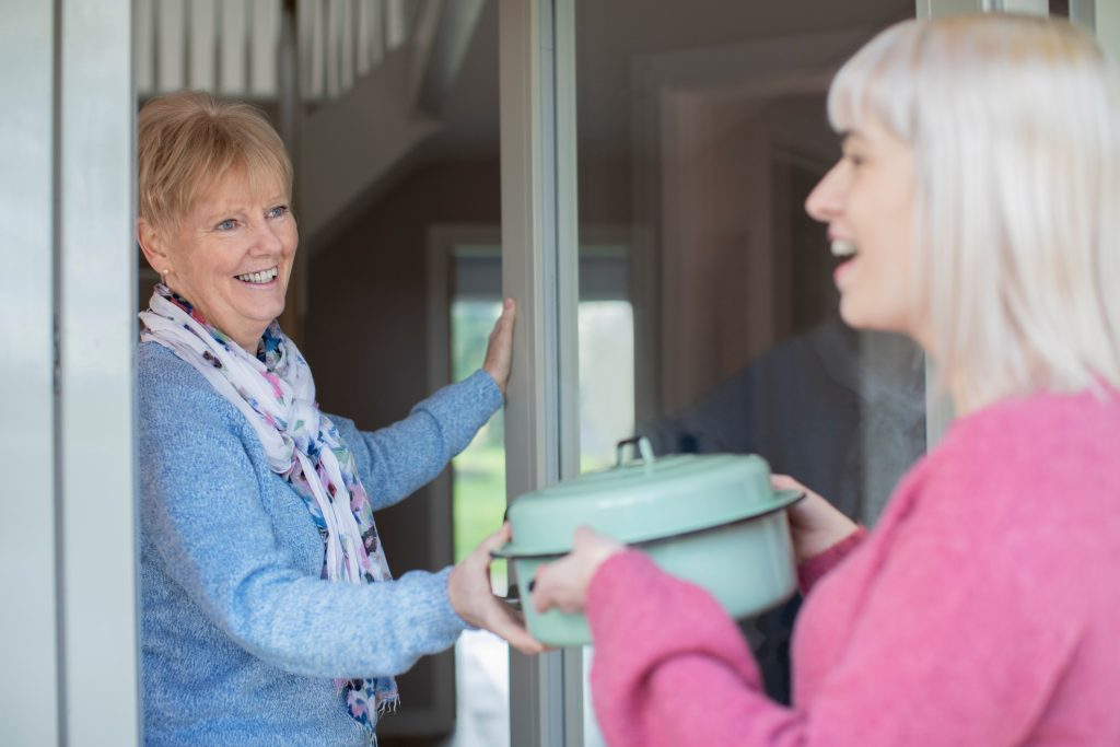 nice Younger Woman Bringing Meal For Elderly Neighbour At Home