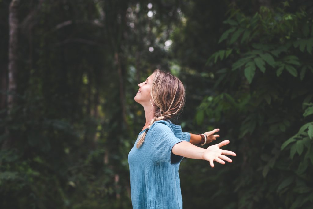 woman with arms stretched out in forest