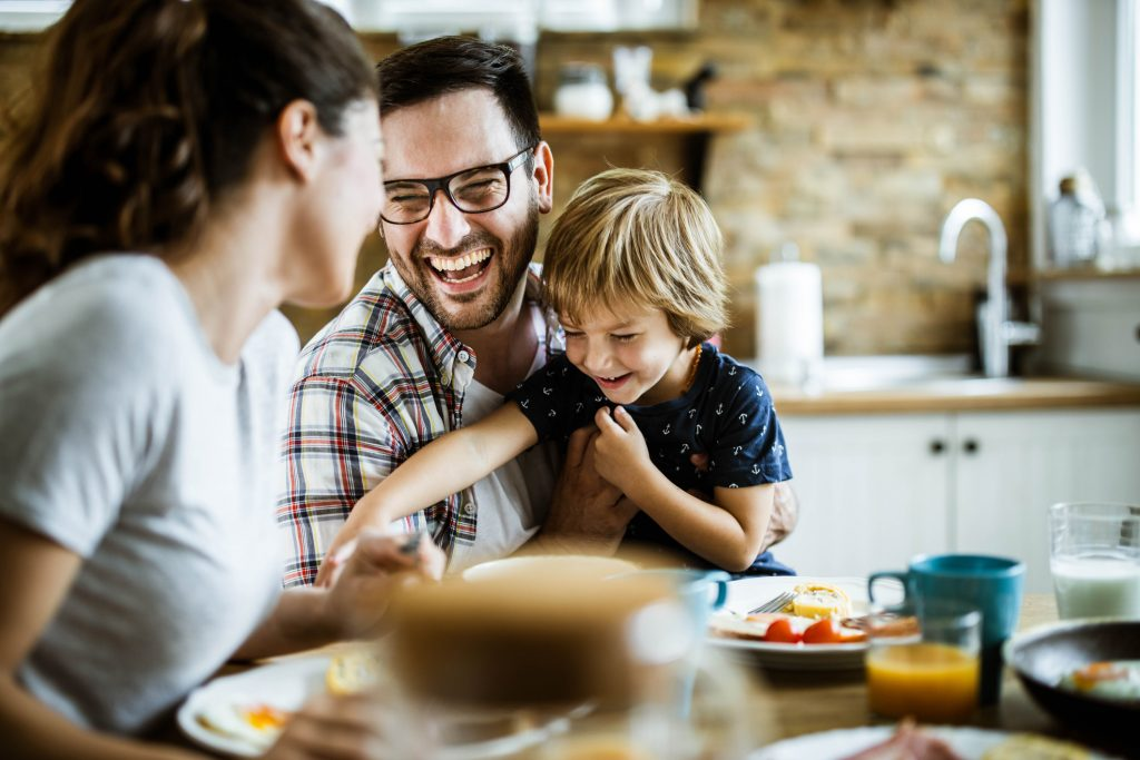 Cheerful family having fun, taking time to laugh during their meal at dining table.
