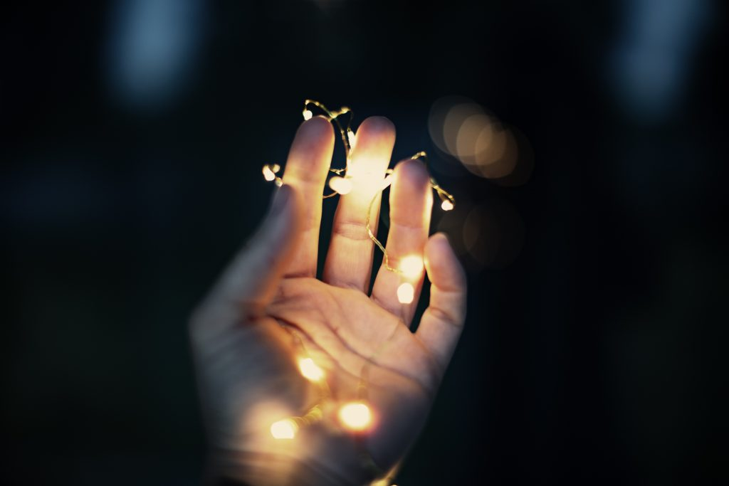 a woman holding string lights in her hand in a dark place