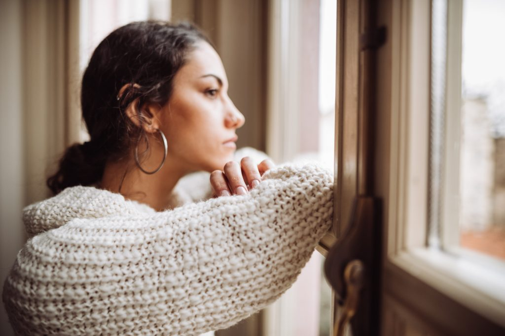 prayerful woman in front of the window