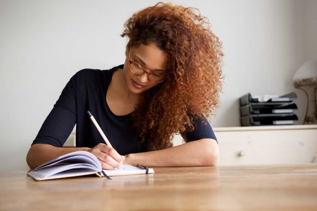 Portrait of woman writing in a journal at home