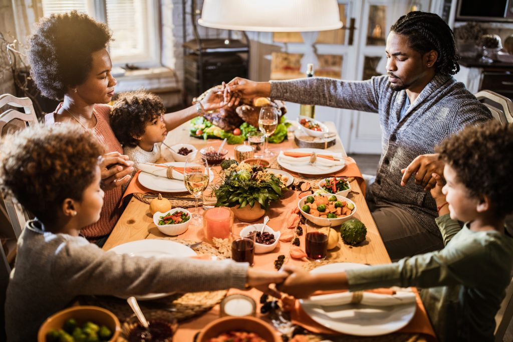 African American family holding hands and praying before their Thanksgiving meal at home.