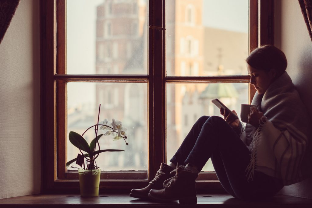 Woman on the window drinking coffee and surfing the net on smartphone