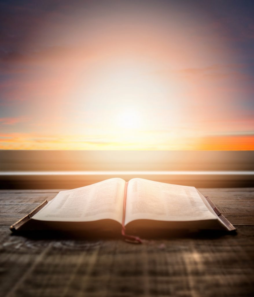 Close up open Bible, with dramatic light. Wood table with sun rays coming through window. Christian image