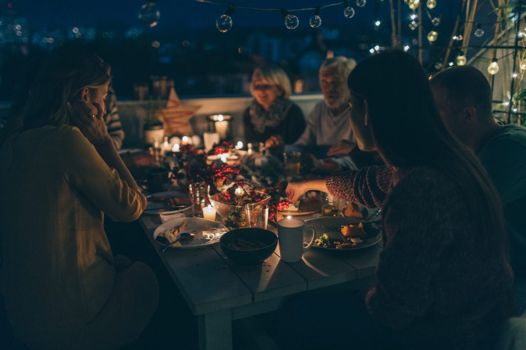 Photo of a multi-generation family having candlelit Christmas dinner, celebrating traditions