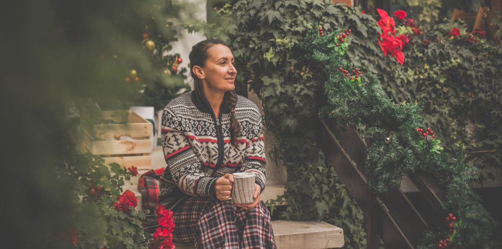 adult woman is sitting on staircase, and having tea in her pajamas during Christmas time.