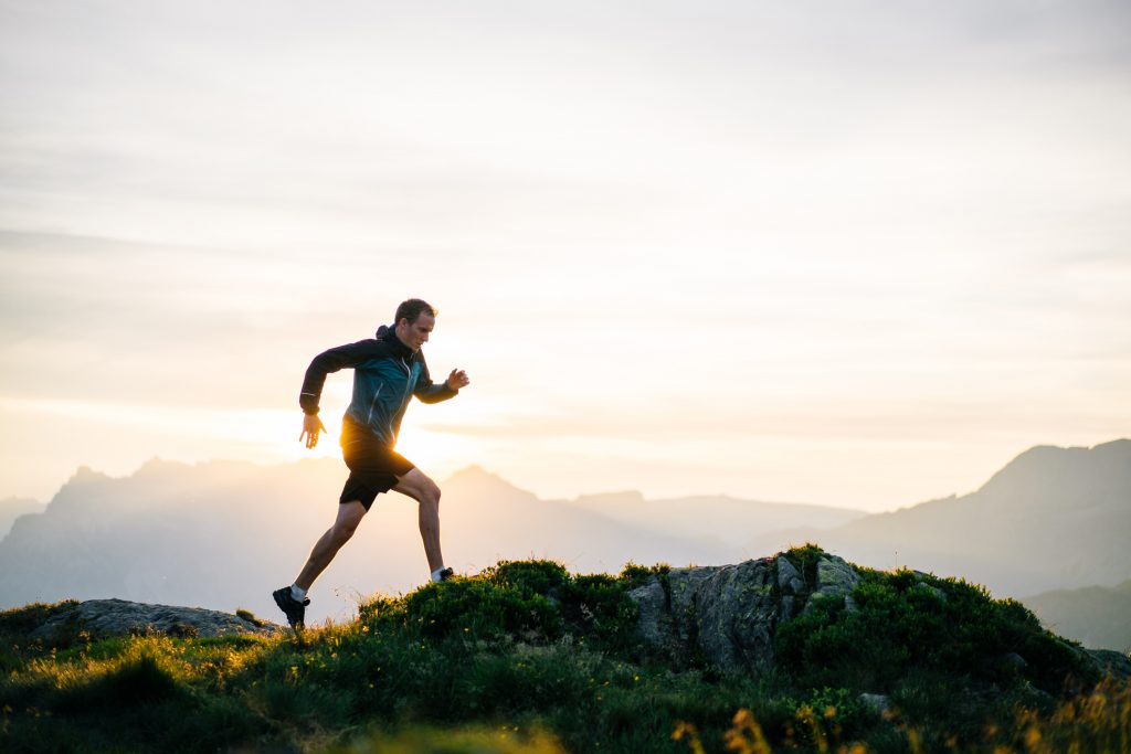 Young man fulfills his new years resolution, runs on mountain ridge at sunrise