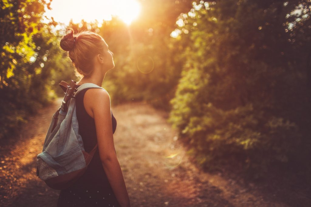 Photo of a young woman with a backpack, wandering around in nature and relaxing, getting encouraged