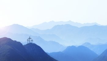Three crosses on a hill at sunrise symbolize the Crucifixion of Christ as the sun rises in the distance. A series of mountain ridges disappear into the horizon
