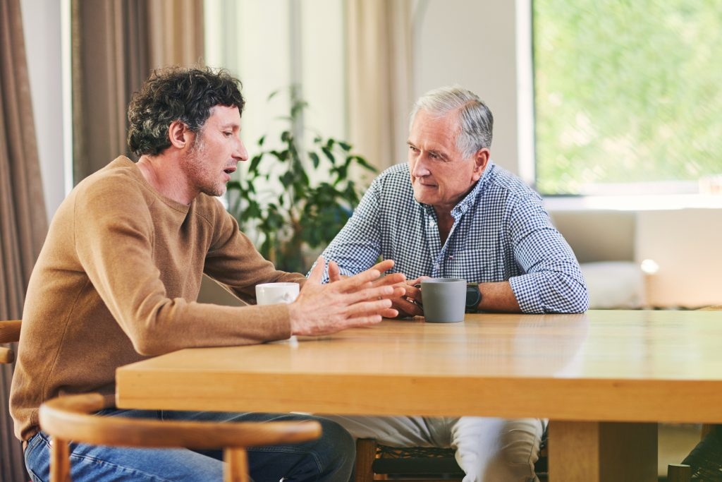 Shot of a two men having a chat in a home