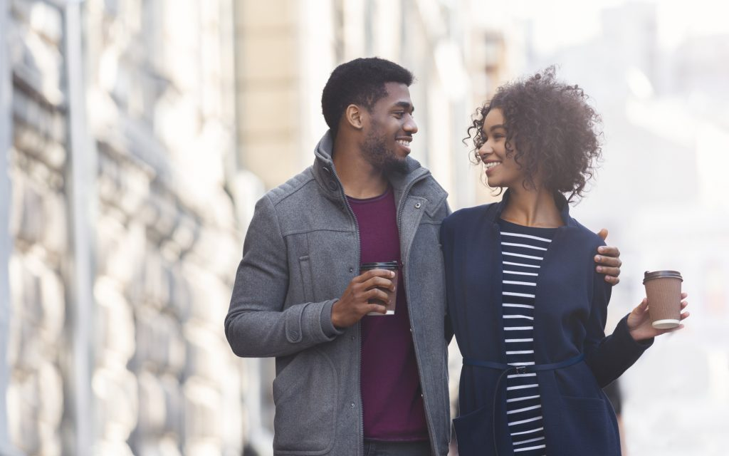 African american man and woman drinking coffee outdoors