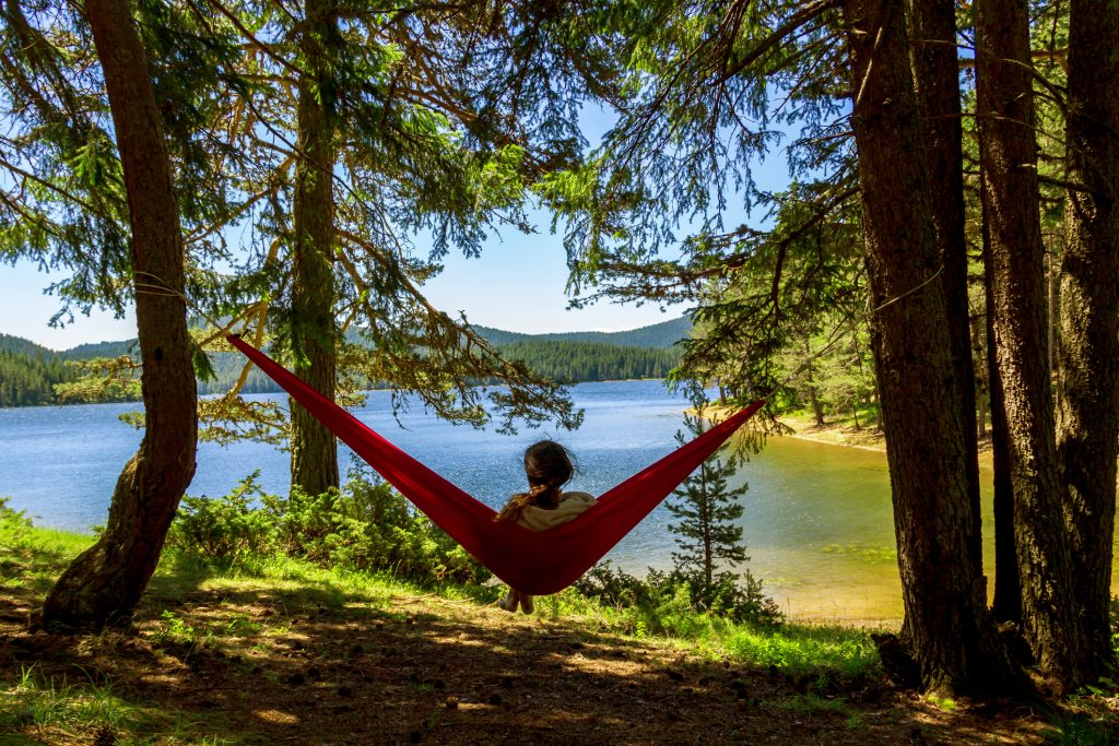 tired girl finding rest in a hammock with a beautiful nature view