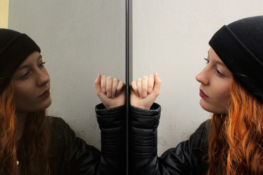 Girl with long red hair wearing a black woolen cap and a black leather jacket looking at herself mirrored on a glass door with a thoughtful expression.
