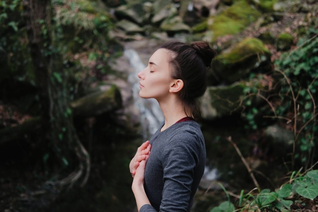 Young woman breathing deeply outdoors in moss forest on background of waterfall.