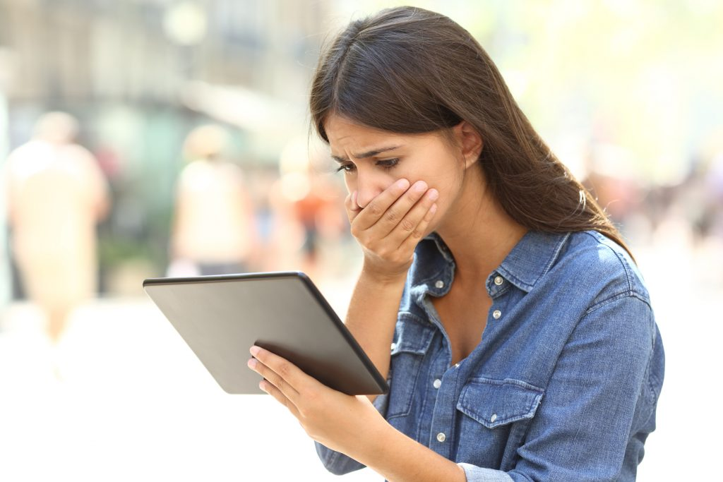 woman emotionally responding to what she sees on a tablet