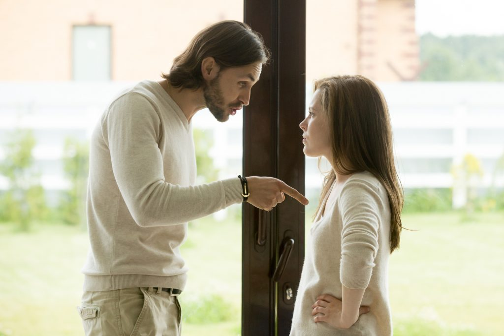 Unhappy couple arguing standing at house door, husband pointing finger in blame