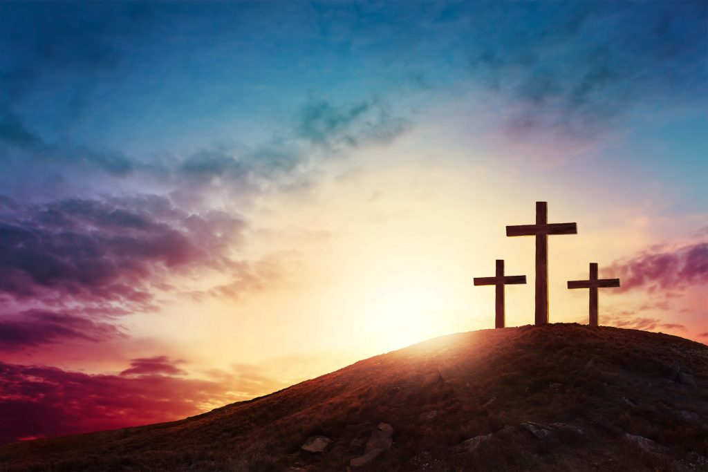Silhouette cross on Calvary mountain sunset background.