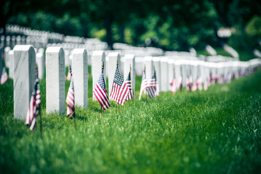 American flags by headstones on Memorial Day in Arlington National Cementery, Washington DC. USA.