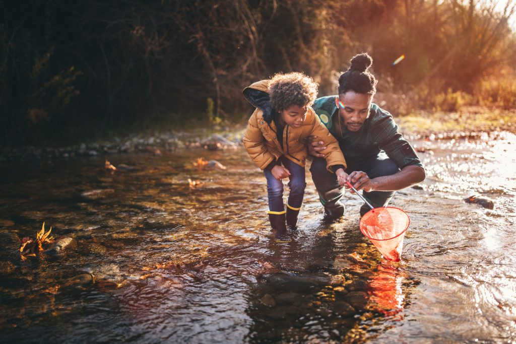 Young father teaching son how to fish with fishing net in mountain stream at sunset