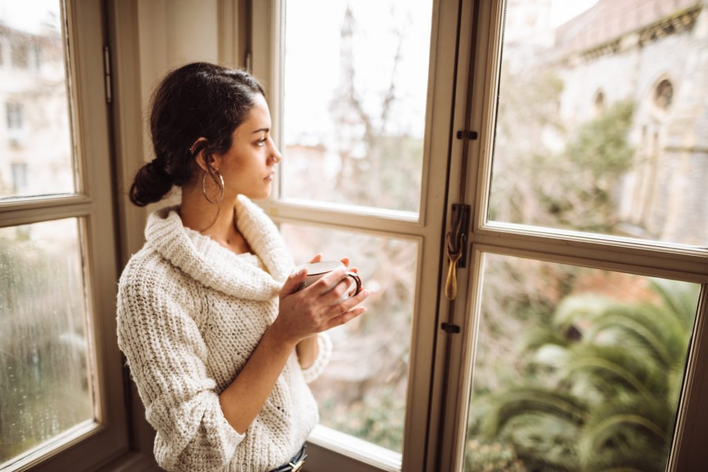 sad woman holding coffee mug looking out window