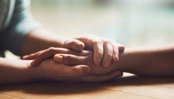 Friends holding hands in comfort