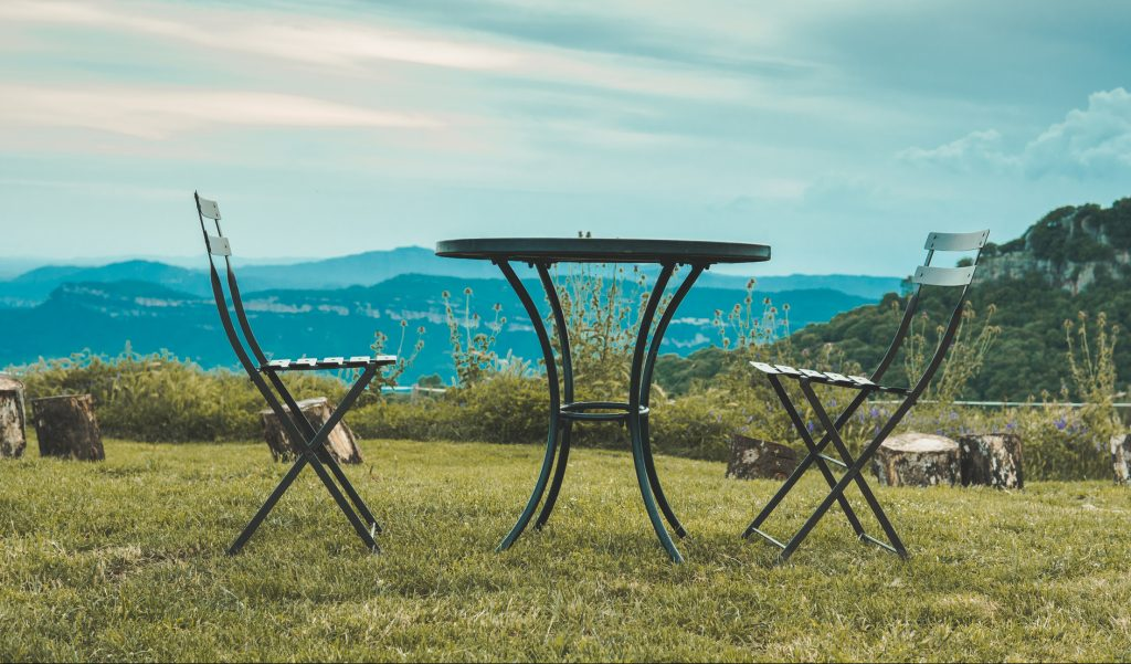 Two chairs facing each other and a table in the middle of nature. Behind it you can see the mountains and the clouds. They are high in a valley.