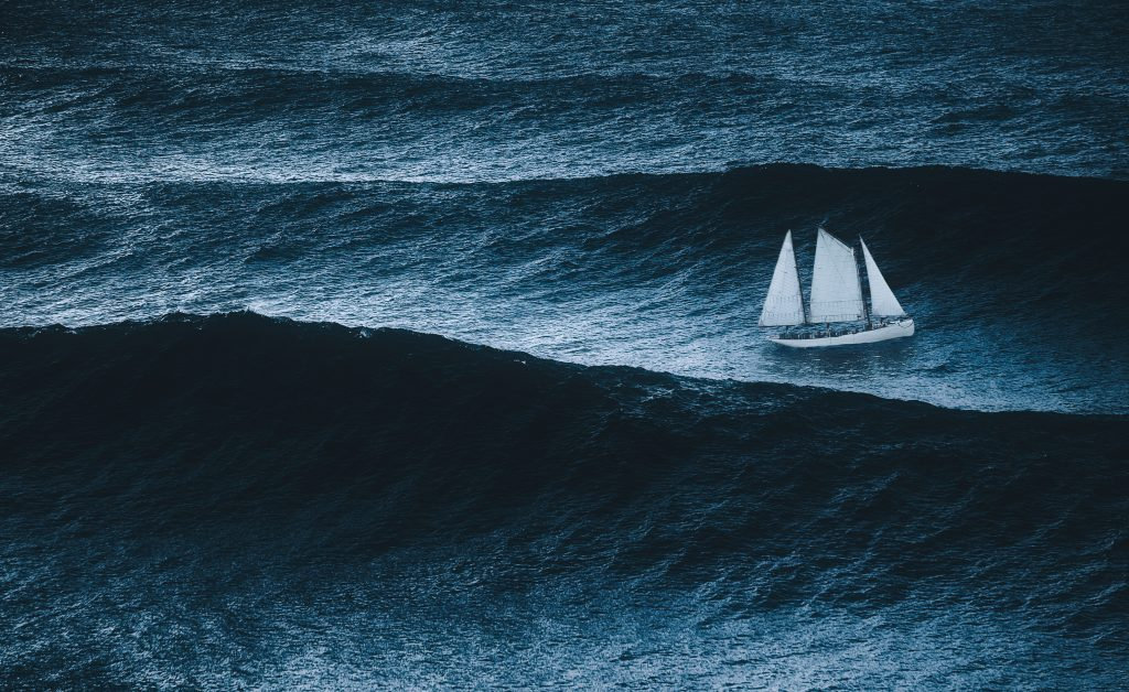 sailboat on the sea with storm and big waves, waves of grief