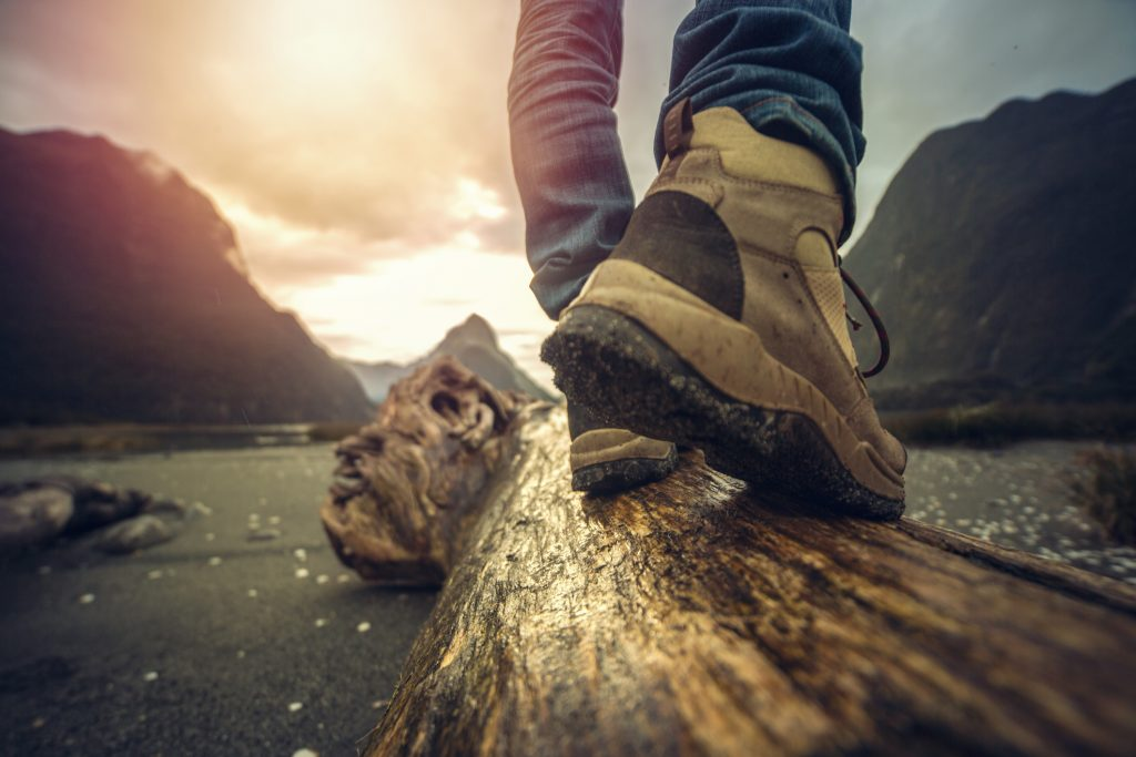 Low angle view of man's legs and hiking boots standing on tree log. Mitre peak on the background, South Island, New Zealand.