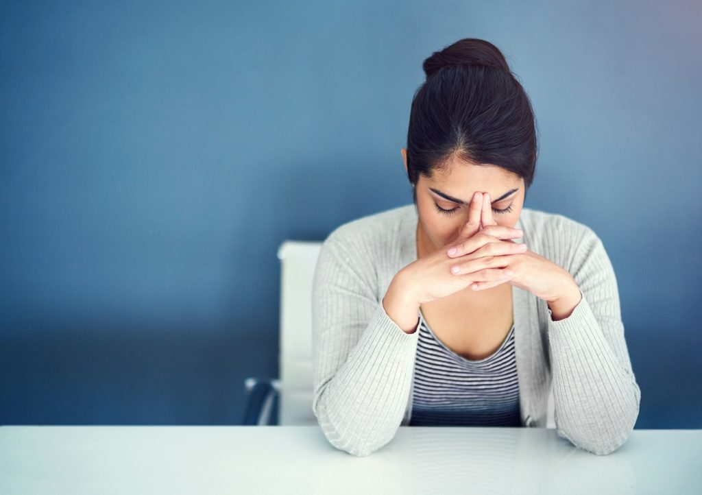 Shot of an overwhelmed young businesswoman holding her head in her hands while sitting at her desk and wrestling with rejection