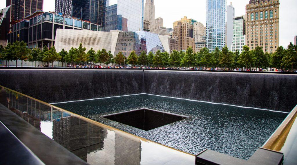 National September 9/11 memorial waterfalls with surrounding buildings in Lower Manhattan.