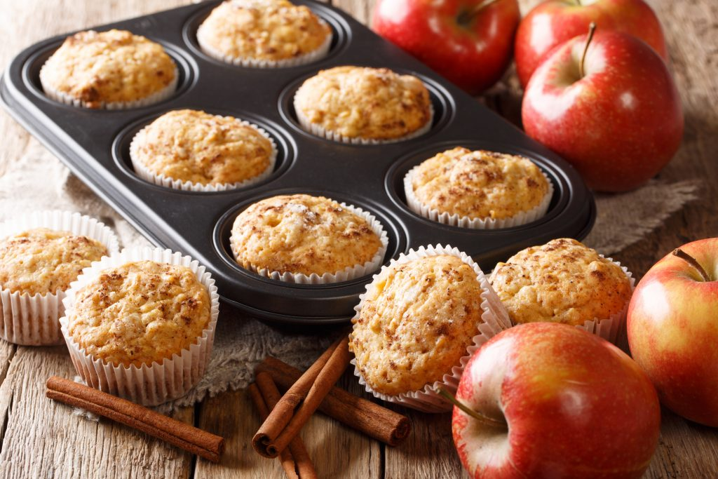 Sweet dessert apple muffins with cinnamon close-up in a baking dish on the table.